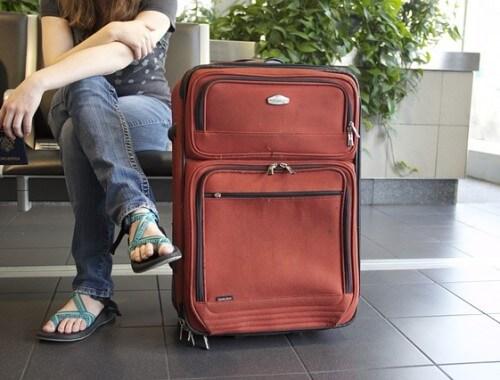 kobieta siedząca z walizką na lotnisku