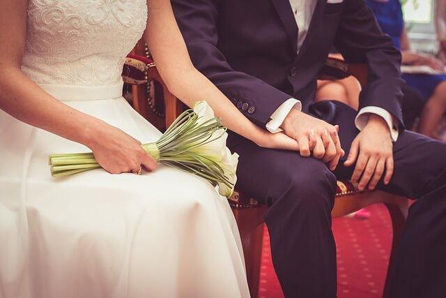 Kobieta w białej sukni ślubnej z mężczyzną w garniturze na czerwonym dywanie
